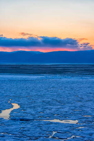 sunset over Lake Baikal in the spring, ice on the lake