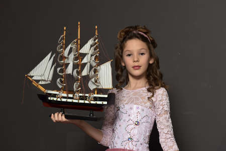 young girl, a princess standing in a pink retro dress with a toy ship sailing in her hands