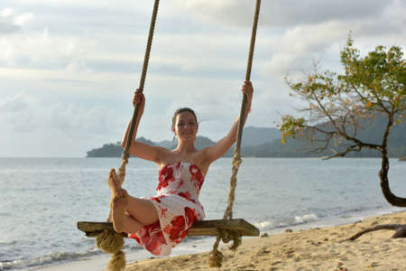 Girl in white with red flowers dress on the beach on a swing