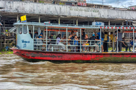 BANGKOK, THAILAND - 20,08,2018: River boat transporting passengers and tourist down Chao Praya river. Still a popular method of transporting passengers, the river connects to lots of smaller canals.