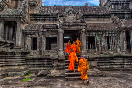 Siem Reap, Cambodia - 29.06.2017 - Monks walk quietly inside the Angkor Wat Temple, the most famous temple of Cambodia