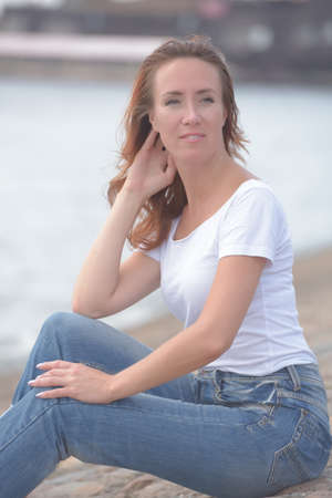 woman in jeans and white t-shirt sits by the water