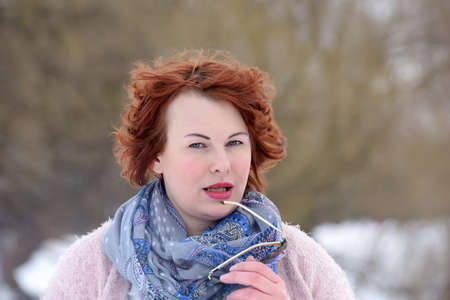 portrait of a red-haired woman of forty years on the winter background