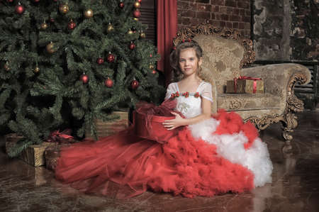 young princess in red and white dress in christmas