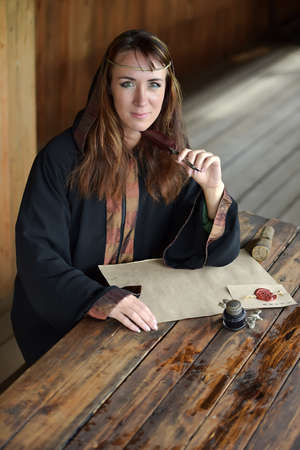 A woman in a medieval cloak sits with a pen and writes