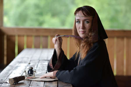 A woman in a medieval  with a pen and writes.