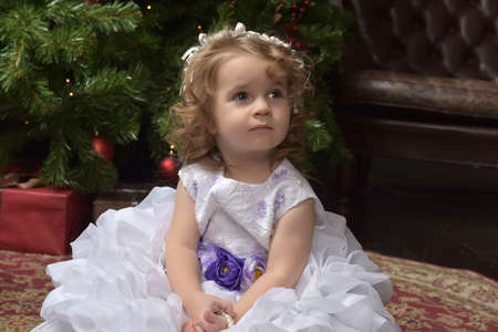 young girl little princess in a white festive dress with a blue belt