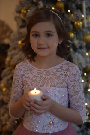 cute young girl in christmas with a candle in her hands Stock Photo