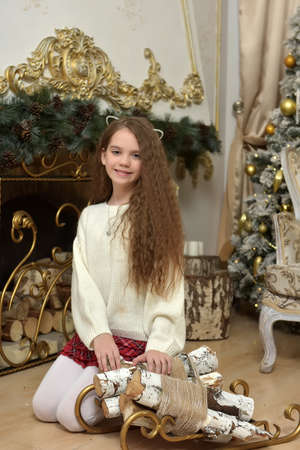 girl child by the fireplace in christmas in the hall with golden decorations