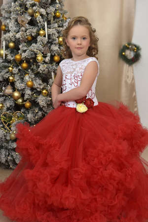 beautiful girl dancing in red with white dress in christmas by the christmas tree