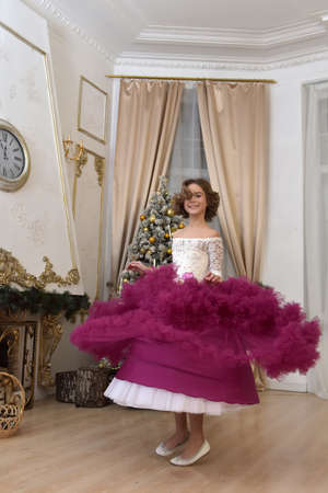 happy girl in a dress at Christmas by the Christmas tree