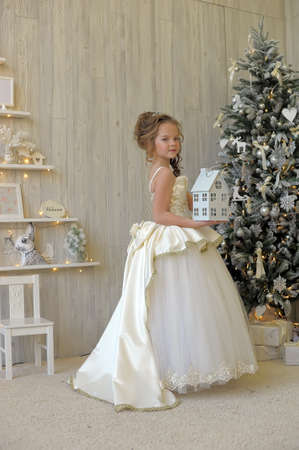 Winter princess in white dress at the Christmas tree