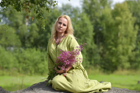 The girl the blonde in vintage clothes of the Viking sits with wild flowers in hands