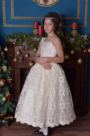 Victorian girl in a white dress in Christmas stands at the Christmas tree