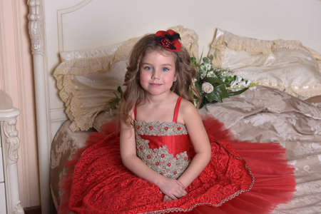 portrait of a little girl princess in a red dress and hat sitting on the sofa Standard-Bild