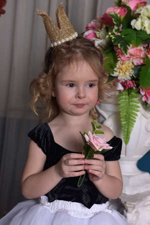 cute little girl with a crown on her head among the flowers