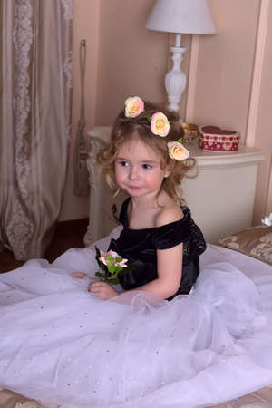 cute little girl with a crown of flowers on her head and flowers in her hands