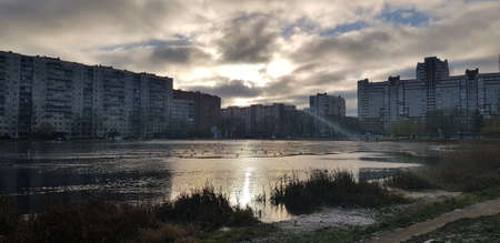 lake in a small park in the city in a modern residential area, covered with the first thin ice in autumn Standard-Bild