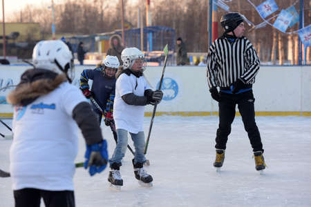 """Russia, Severodvinsk 27,11,2016 Children with hockey sticks playing hockey at the festival """"Hockey Day"""" outdoor street festival"""