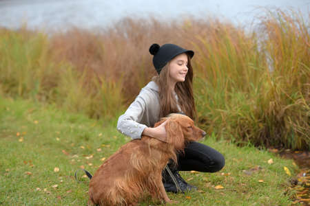 happy girl in the park with a spaniel in the fall by the lake