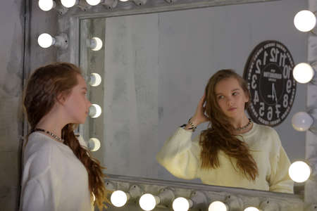 Portrait of a girl in a white sweater in the backlit mirror