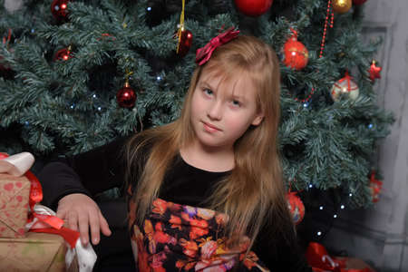 girl blonde child in black with red dress in christmas by the christmas tree alone