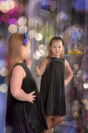 girl blonde child in a black dress looks at herself in the mirror