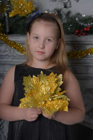 blonde teen girl in black dress in christmas time with a golden flower in her hands in christmas