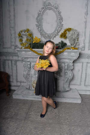 blonde teen girl in black dress in christmas time with a golden flower in her hands in christmas Stock Photo