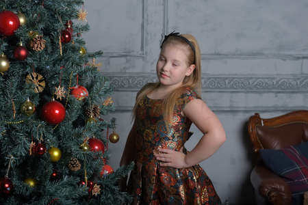 girl blonde child in a golden dress in christmas