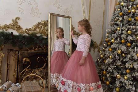 teen blonde in gorgeous white with pink dress by the mirror at christmas