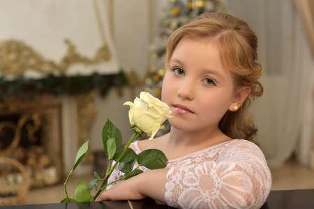 Retrato de una adolescente rubia con una rosa blanca en una blusa de encaje