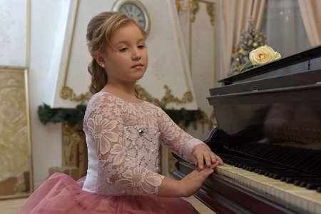 teen blonde in gorgeous white with pink dress by the piano