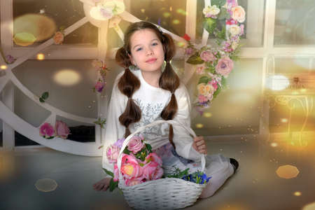 brunette girl with a wicker basket with flowers in the studio 스톡 콘텐츠