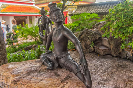 Statues of hermit at showing a posture of massage therapy at Temple of Reclining Buddha or Wat Pho, Bangkok, Thailand.