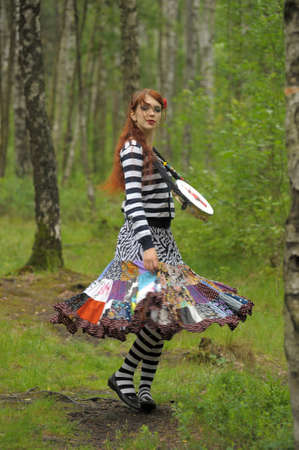 red-haired gypsy with a tambourine in the forest