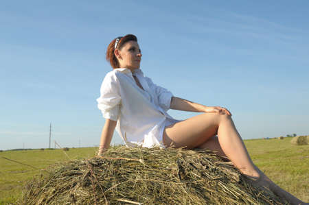 woman in a white shirt on a haystack in the summer field