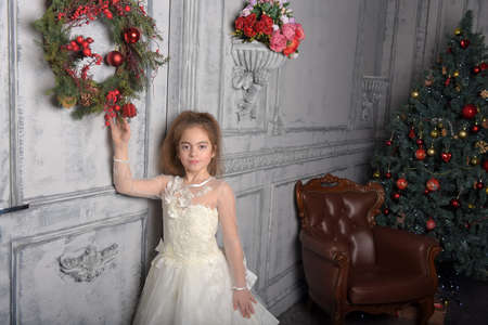 girl in white dress next to christmas wreath on the door Stok Fotoğraf