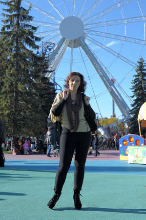 woman in the amusement park on the background of the carousel