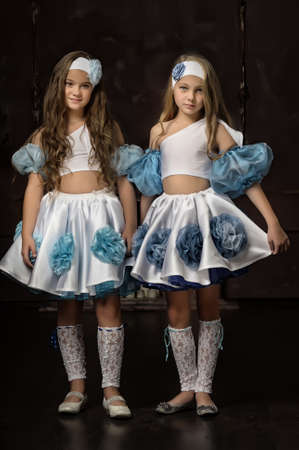 two girls in blue with white tops and skirts Stockfoto