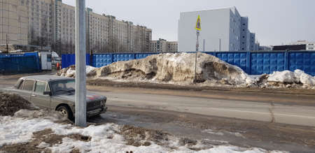Russia, St. Petersburg 15,02,2019 snowdrifts in winter on the street along the fence and the road and parked cars Redactioneel