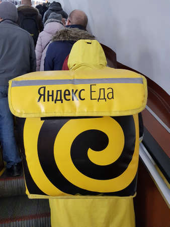 Russia, St. Petersburg 17,03,2019 Spreader Yandex food on an escalator in the subway