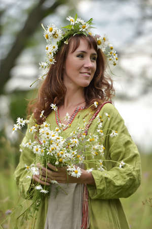 Slav woman in a green dress with a wreath of daisies in her hair and a bouquet of daisies in her hands 版權商用圖片