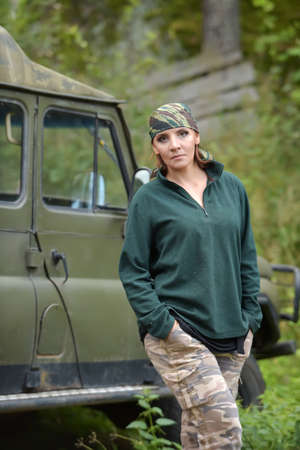 Woman wearing camouflage bandana against the backdrop of UAZ. Fashion, brave.
