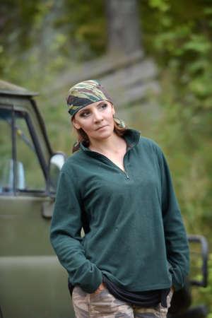 Woman wearing camouflage bandana against the backdrop of UAZ. Fashion, brave.