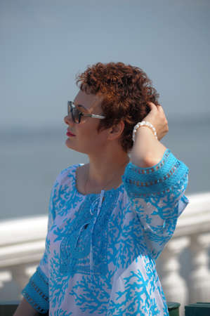 red-haired woman in summer with a short haircut and sunglasses in a blue blouse Imagens