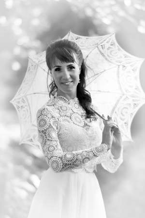 Elegant brunette in a vintage white dress with an umbrella in the park