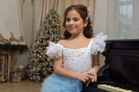 sweet girl young princess in white with a blue dress and a barrette in black hair curls at the piano