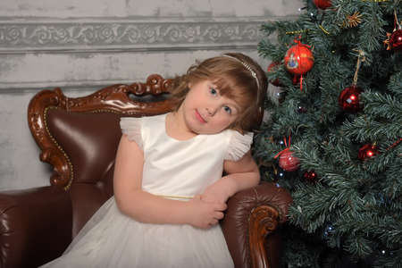 girl in white dress sits in an old chair by the Christmas tree