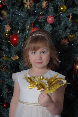 a girl in a white dress with a funny facial expression and a big Christmas gold flower by the Christmas tree Standard-Bild - 122690504